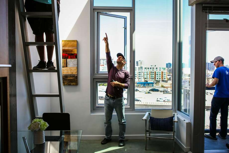 Ro-El Cordero (left), Jason Schmidt and Andrew Buck explore a tiny apartment during an open house at the Cubix building in San Francisco. Photo: Gabrielle Lurie, Special To The Chronicle