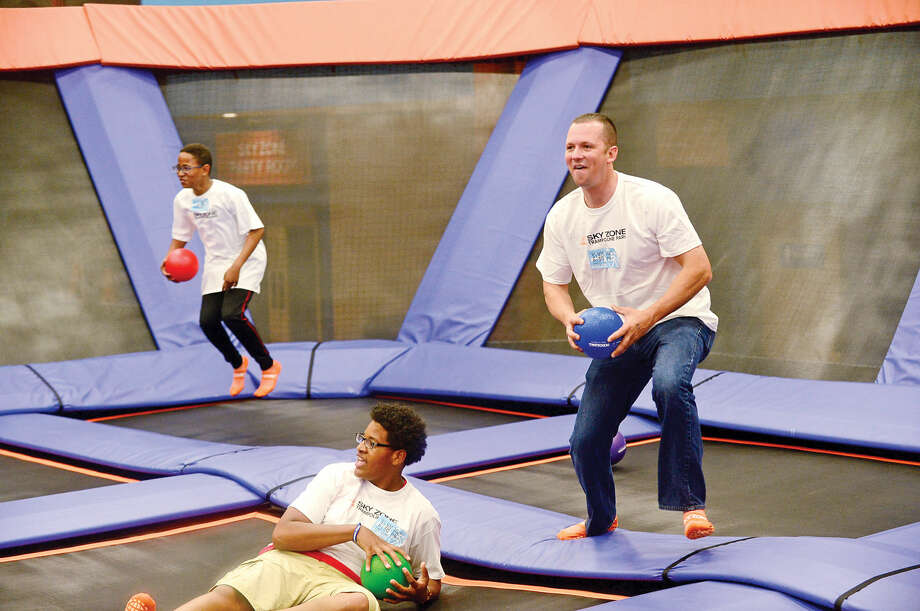 Norwalk police officer Gabriel DeMott, right, and members of the youth group under the umbrella of Juvenile Review Board, including Calvin Reynoso and Clive Bey, participate in activities at Sky Zone as part of a mentoring program between police and kids. Photo: Erik Trautmann