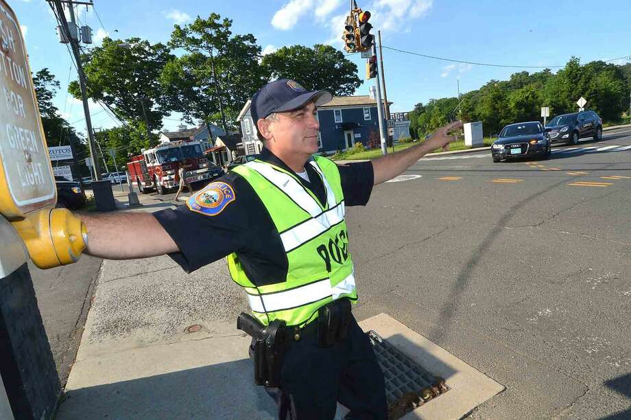 Westport Police Detective Phil Restieri motions to drivers to make the right turn on red onto Bridge st over the Saugatuck River bridge during rush hour traffic on Tuesday May 31 in Westport Conn. Photo: Alex Von Kleydorff