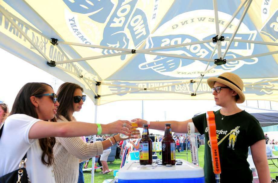 Right, Emily Sauter, of Two Roads Brewery in Stratford, gives samples to Alyssa Mantilla, of New Haven, and her friend Devon McKenna, of Fairfield, during the Harbor Brew Fest in Bridgeport. Two Roads will be one of the vendors at the Brews on Bedford festival in Stamford next month. (Photo: Christian Abraham)