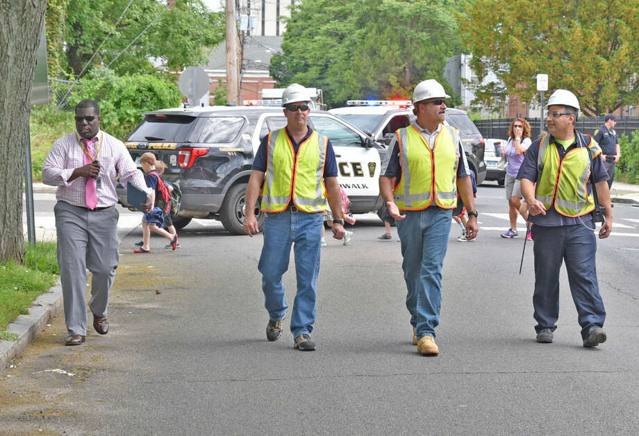 The principal of Columbus Magnet, Medard Thomas, with Eversource workers Tuesday, May 31, 2016. About 340 students were evacuated from the Columbus Magnet School on Chestnut Street after a gas line was struck and severed at a nearby business. (Photo: Harold F. Cobin)