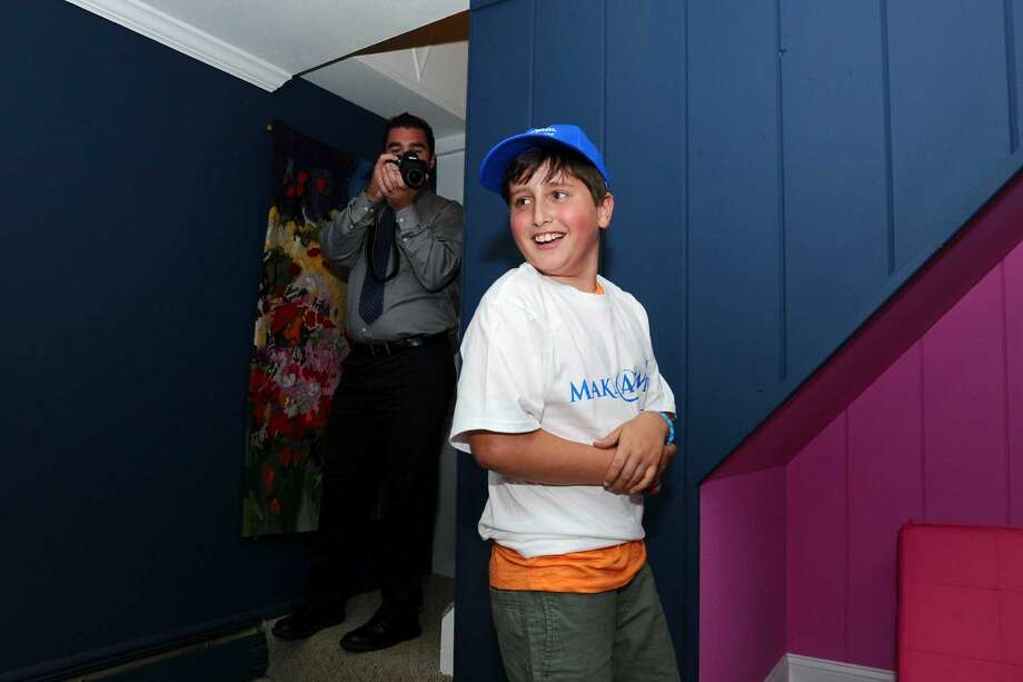 Eli Schwartz, 8, of Stamford, smiles as we walks into his new man cave for the first time. Photo: Michael Cummo