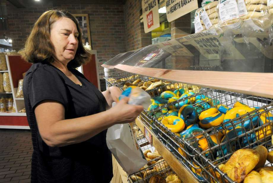 Renee Coleman of Monroe buys a blue and orange bagel for her small granddaughter who was attracted to the colors, Tuesday, June 7, 2016. Stew Leonard's in Danbury is making bagels in school colors - blue and gold for Brookfield and blue and orange for Danbury High School. (Photo: Carol Kaliff)