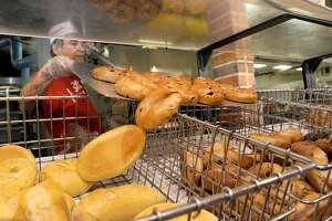 Miguel Porto, a bagel baker at Stew Leonard's in Danbury, adds freshly baked bagels to the store display Tuesday, June 7, 2016. Stew Leonard's in Danbury is making bagels in school colors - blue and gold for Brookfield and blue and orange for Danbury High School. (Photo: Carol Kaliff)