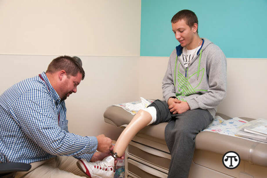 Darren Rottmann fitting a patient for a new prosthetic. (NAPS)