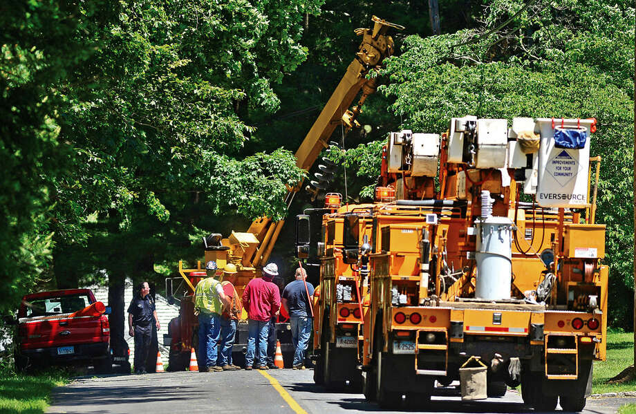 Wilton Police and Eversource employees investigate a workplace accident scene on Rivergate Drive in Wilton, Conn. where a utility worker was injured Thursday, June 9, 2016. Photo: Erik Trautmann