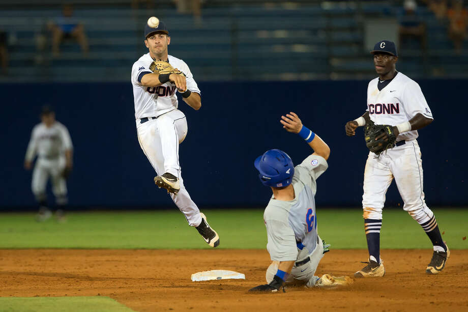 UConn's Bryan Daniello, left, turns a double play during his team's NCAA tournament game against Florida. Daniello hails from Norwalk. Photo: Stephen Slade