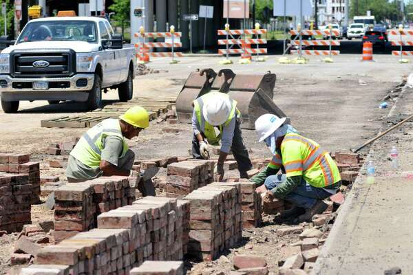 Construction workers remove and stack bricks from the Yale Street Bridge on a pallet. A group of Heights residents have formed a group to save the bricks and other original pieces of the historic structure from the landfill.