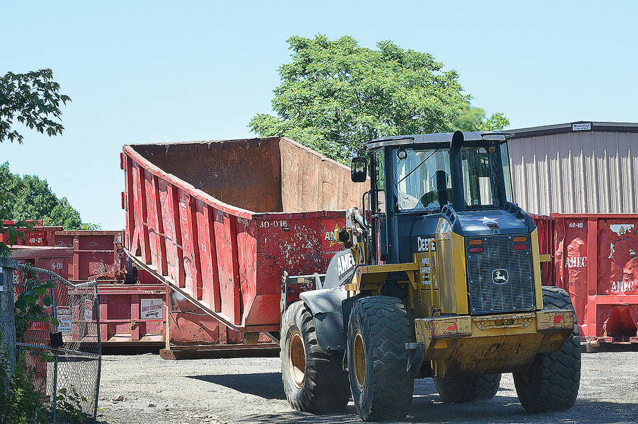 Workers use a loader to move containers at the AMEC Carting site on Chestnut St. on Tuesday June 14 2016 in Norwalk Conn. Photo: Alex Von Kleydorff