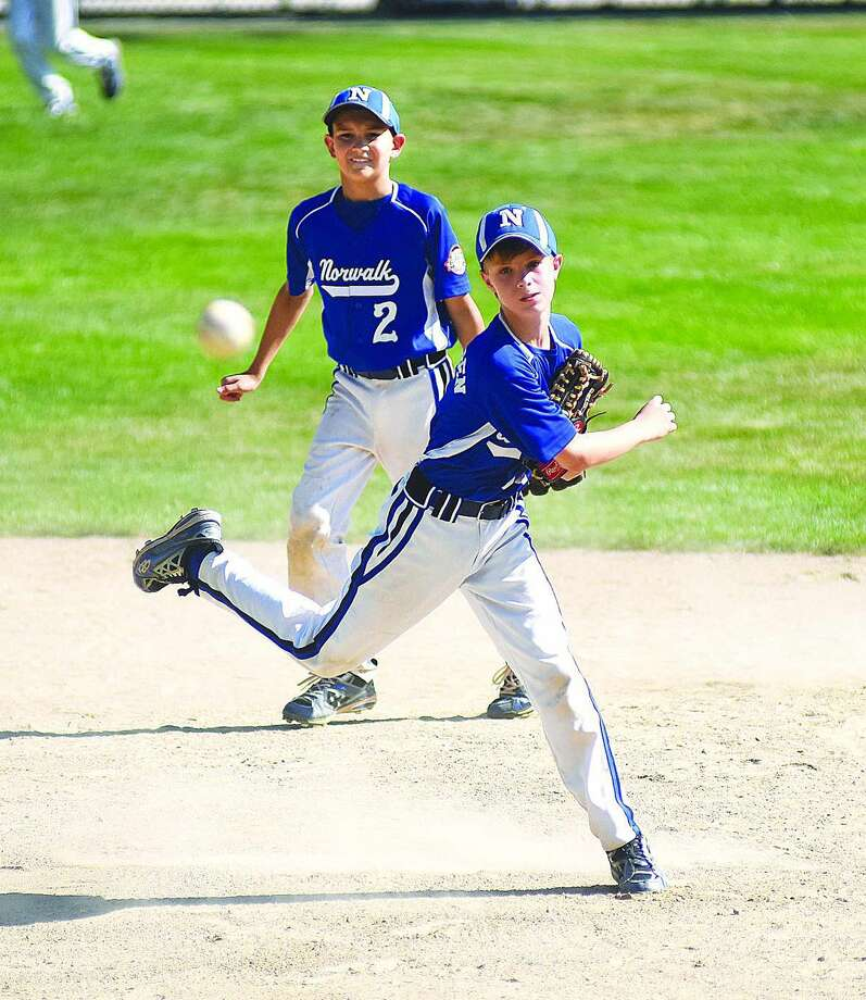 Norwalk second baseman Brendan Edvardsen, front, fires the ball to first base as shortstop Ben Boccanfuso looks on during Norwalk 11-year-old Cal Ripken New England regional game vs. Swanzey, N.H.., at Keyes Field in Dover, N.H. The team is now playing U-12 and starts this summer season on Saturday by hosting the district tournament. Photo: John Nash