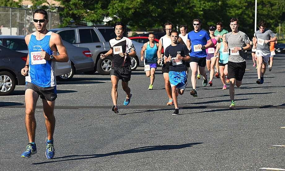Norwalk resident Geoffrey Williams, far left, leads the pack less than a quarter mile into Saturday's Lightfooting Running Club's series-opening three miler at Norwalk High School. Williams ran a 16:56 to win his first series race. Photo: John Nash