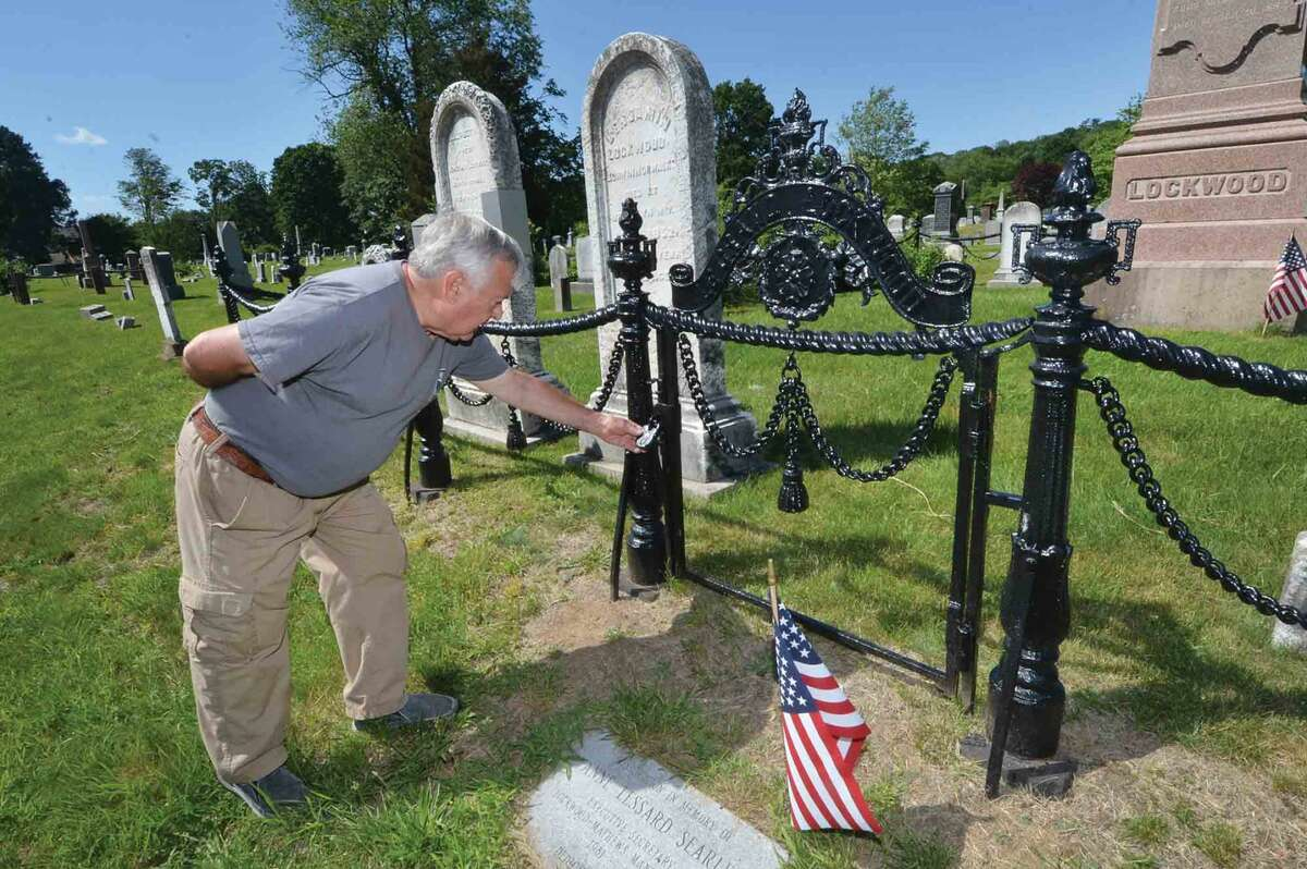 Charlie Williams checks on an old padlock on the recently repaired iron work at the Legrand Lockwood family burial plot in Union Cemetery on Thursday June 9 2016 in Norwalk Conn.