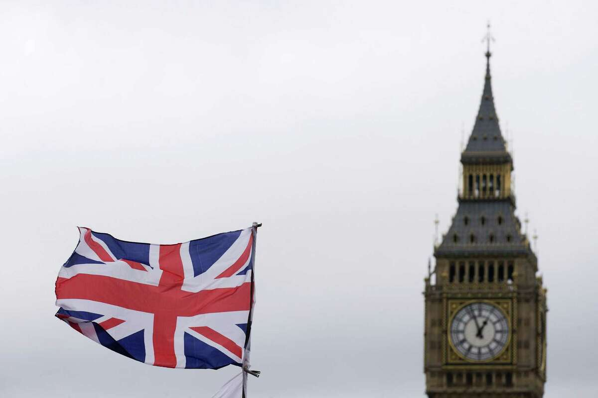 A Union flag flies in the wind in front of the Big Ben clock face and the Elizabeth Tower at the Houses of Parliament in central London. Brittain's vote to leave the European Union sent global markets tumbling and increased the risk of a global recession to 50 percent, according to mutual fund company T. Rowe Price.