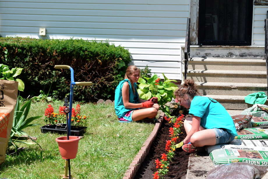 Jessica Haynes | jhaynes@mdn.net Midland residents Rachel Falardeau, left, and Jacqueline Laurin plant flowers as part of a landscaping project on Roberts Street in Saginaw during One Week, One Street. It is Laurin's first time volunteering for the five-day neighborhood project, and Falardeau's second time volunteering.