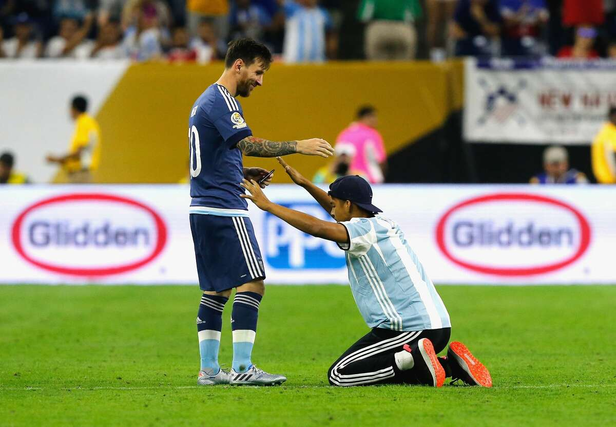 HOUSTON, TX - JUNE 21: Lionel Messi #10 of Argentina interacts with a fan who ran onto the field prior to the start of the second half during a 2016 Copa America Centenario Semifinal match between Argentina and the United States at NRG Stadium on June 21, 2016 in Houston, Texas. (Photo by Bob Levey/Getty Images)