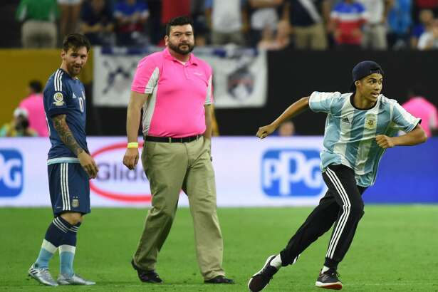 A fan of Argentina's Lionel Messi runs after getting onto the field to greet him before the start of the second half of the Copa America Centenario semifinal football match against USA in Houston, Texas, United States, on June 21, 2016.  / AFP / Mark RALSTON        (Photo credit should read MARK RALSTON/AFP/Getty Images)