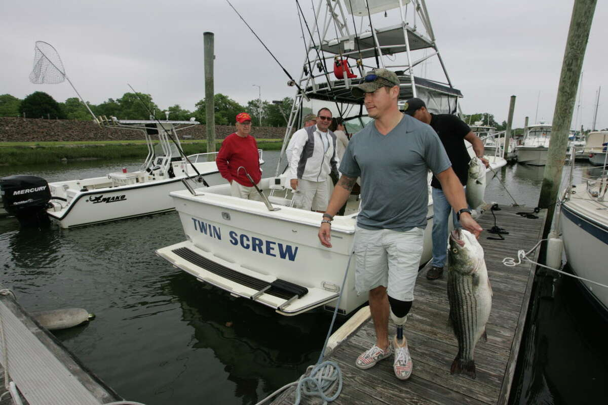 Sergio Cano, a wounded warrior participant, carries his catch off to be weighed in during the Hooks for Heroes Charity Fishing Tournament at the Halloween Yatch Club in Stamford, Conn on Saturday, June 20, 2015.
