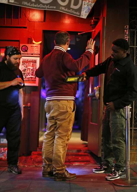 QBar doormen Wahid Brown (right) and Cain (left) perform a security check on a patron Tuesday eveningl. Photo: Scott Strazzante, The Chronicle