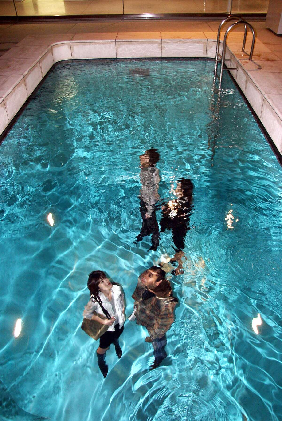 In an undated photo, Japanese couples look through a swimming pool at the 21st Century Museum of Contemporary Art in Kanazawa, in Ishikawa prefecture, northern Japan. The museum, which cost over 10 billion yen, is a UFO-shaped modern complex which opened Oct. 9, 2004, bringing a rare contemporary expression in the heart of traditional Japan.