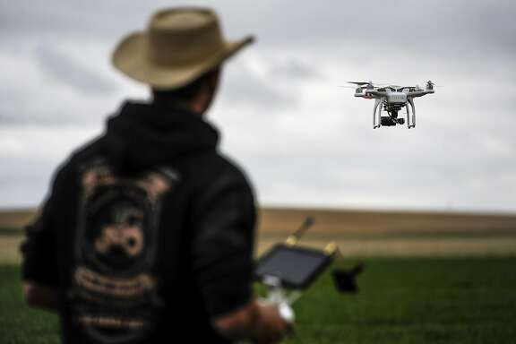 FILE -- An organic farmer uses a drone with a camera to survey 3,500 acres of land for weeds, high yield areas and dry spots, in Northern Colorado, April 27, 2015. The Federal Aviation Administration�s new commercial drone rules allow a broad range of businesses to use drones under 55 pounds, but with several restrictions: The drones must be operated by a pilot who has passed a written test and is at least 16 years old. (Michael Ciaglo/The New York Times)
