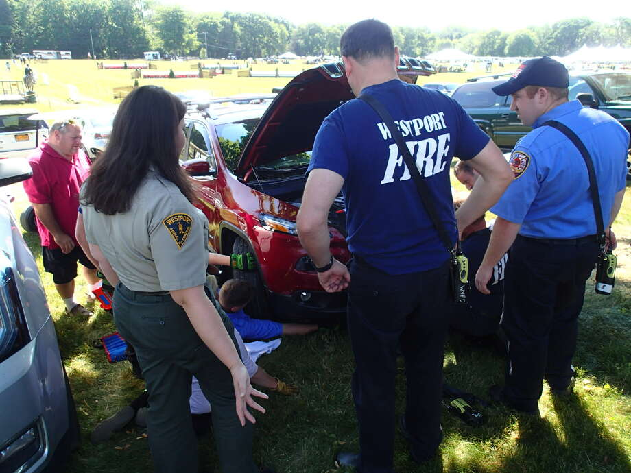 Westport emergency crews work to rescue a cat from a car at the Fairfield County Hunt Club. Photo: Contributed / Contributed Photo / Westport News
