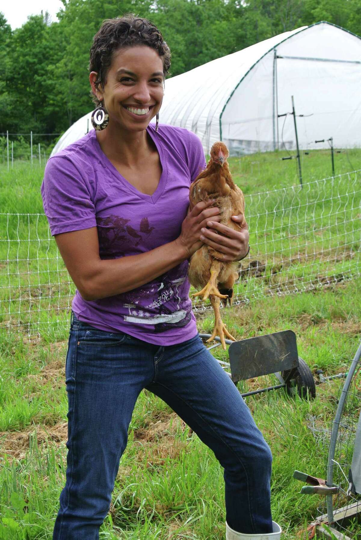 Leah Penniman, co-owner of Soul Fire Farm, poses with a chicken that will be sold for meat at her farm in Grafton. (Deanna Fox)