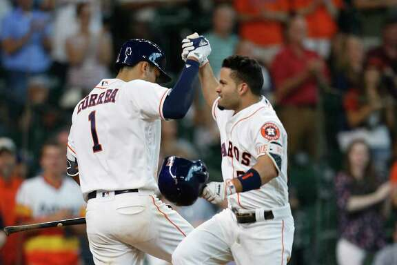 Houston Astros second baseman Jose Altuve (27) celebrates his home run ball with Carlos Correa during the sixth inning of an MLB baseball game at Minute Maid Park, Wednesday, June 22, 2016, in Houston.