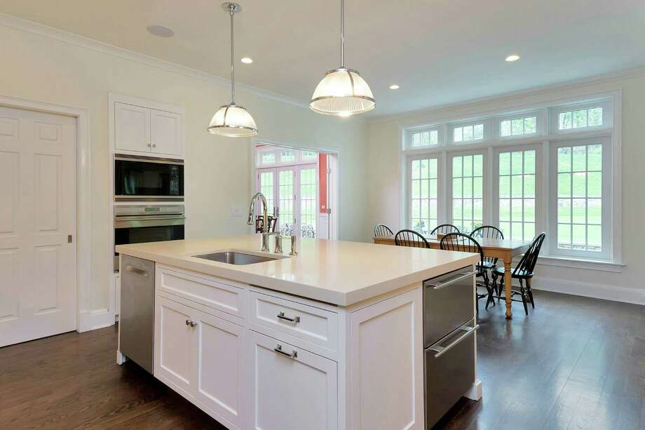 An eat-in kitchen features a timeless design with ivory quartzite counters, floor-to-ceiling subway tile and glass cabinetry. Appliances include a six-burner Wolf range, a Wolf oven, a SubZero refrigerator and two SubZero freezer drawers. Photo: Contributed Photo