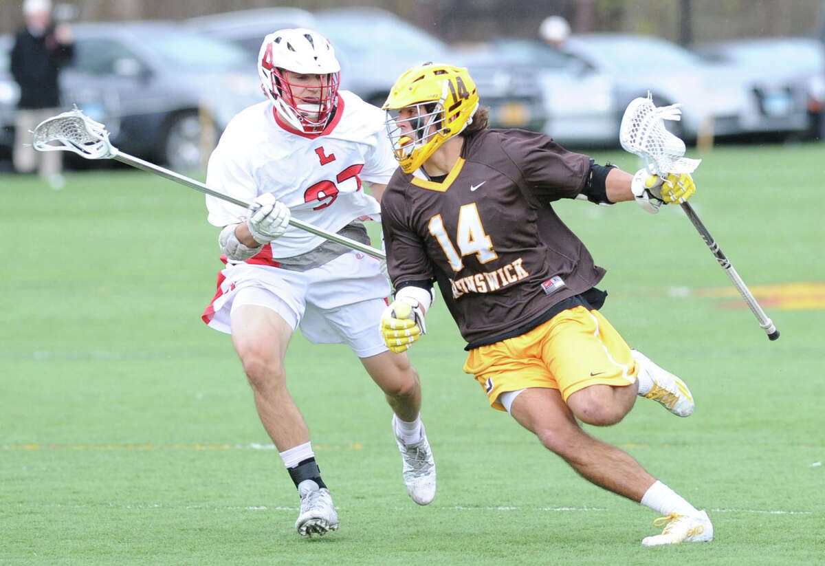 Reilly Walsh (#14), right, of Brunswick blows past a Lawrenceville defender during the boys high school lacrosse match between Brunswick School and Lawrenceville School at Brunswick in Greenwich, Conn., Wednesday, April 22, 2015. Brunswick won the match, 18-8.