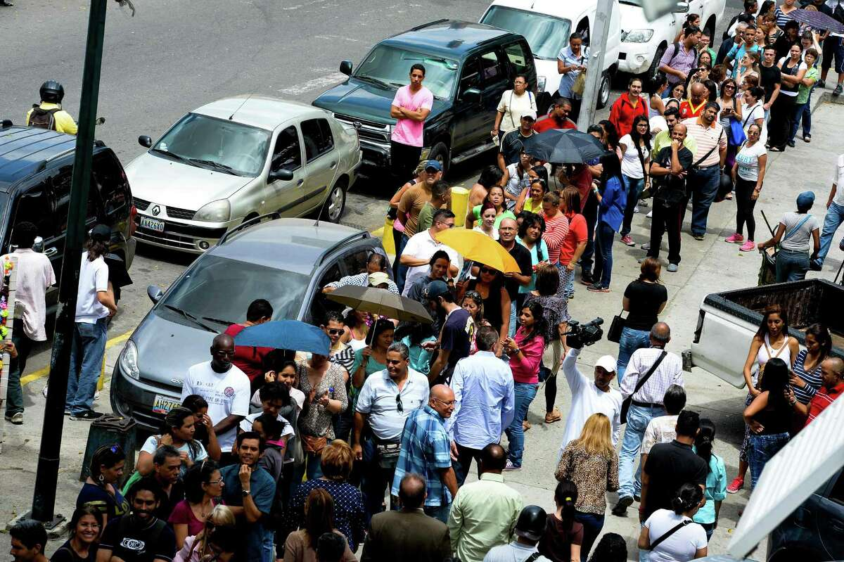 Venezuelans line up to authenticate their signatures for a recall referendum before the National Electoral Council (CNE) in Caracas. Venezuelans queued to get fingerprinted Monday in a crucial phase of efforts to force President Nicolás Maduro from power, after food shortages sparked deadly protests and looting.