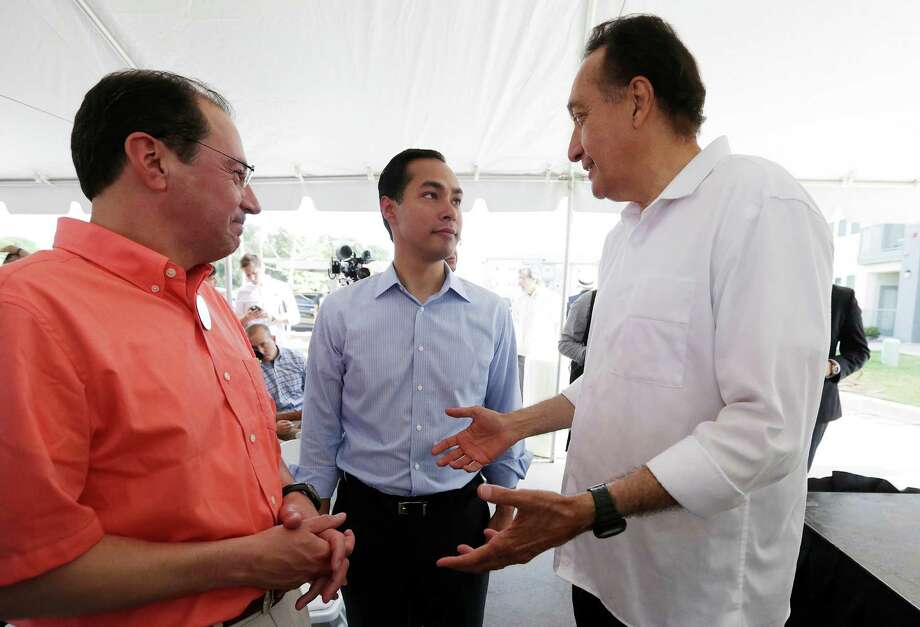 HUD Secretary Julian Castro (center) chats with Henry Cisneros (right) and UTSA's Albert A. Carrisalez (left) during the celebration of the opening of the second Bibliotech named after UTSA President Ricardo Romo at the Gardens of San Juan Square - a San Antonio Housing Authority Community - on Saturday, July 25, 2015. The nation's first all-digital public library, Bibliotech added a second branch in the public housing development located on the city's westside. Romo grew up on the Westside and was honored by having his name emblazoned on the library. Bibliotech gives Bexar County residents access to 38,000 titles which can be accessed via all digital devices and computers. Book titles can also be checked out on e-readers for a two-week period. Gardens of San Juan Square is SAHA's newest mixed-income community that has 539 units. There are currently more than 65,000 registered users of the digital library and over 181,000 on-site visitors to the first location on Pleasanton Road. (Kin Man Hui/San Antonio Express-News) Photo: Kin Man Hui, Staff / San Antonio Express-News / ©2015 San Antonio Express-News