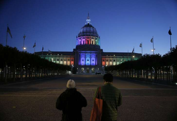 Photographers stop to make some pictures of City Hall as it was awash in the colors of the Rainbow Flag for Pride Week in San Francisco, Calif., on Wednesday, June 22, 2016.