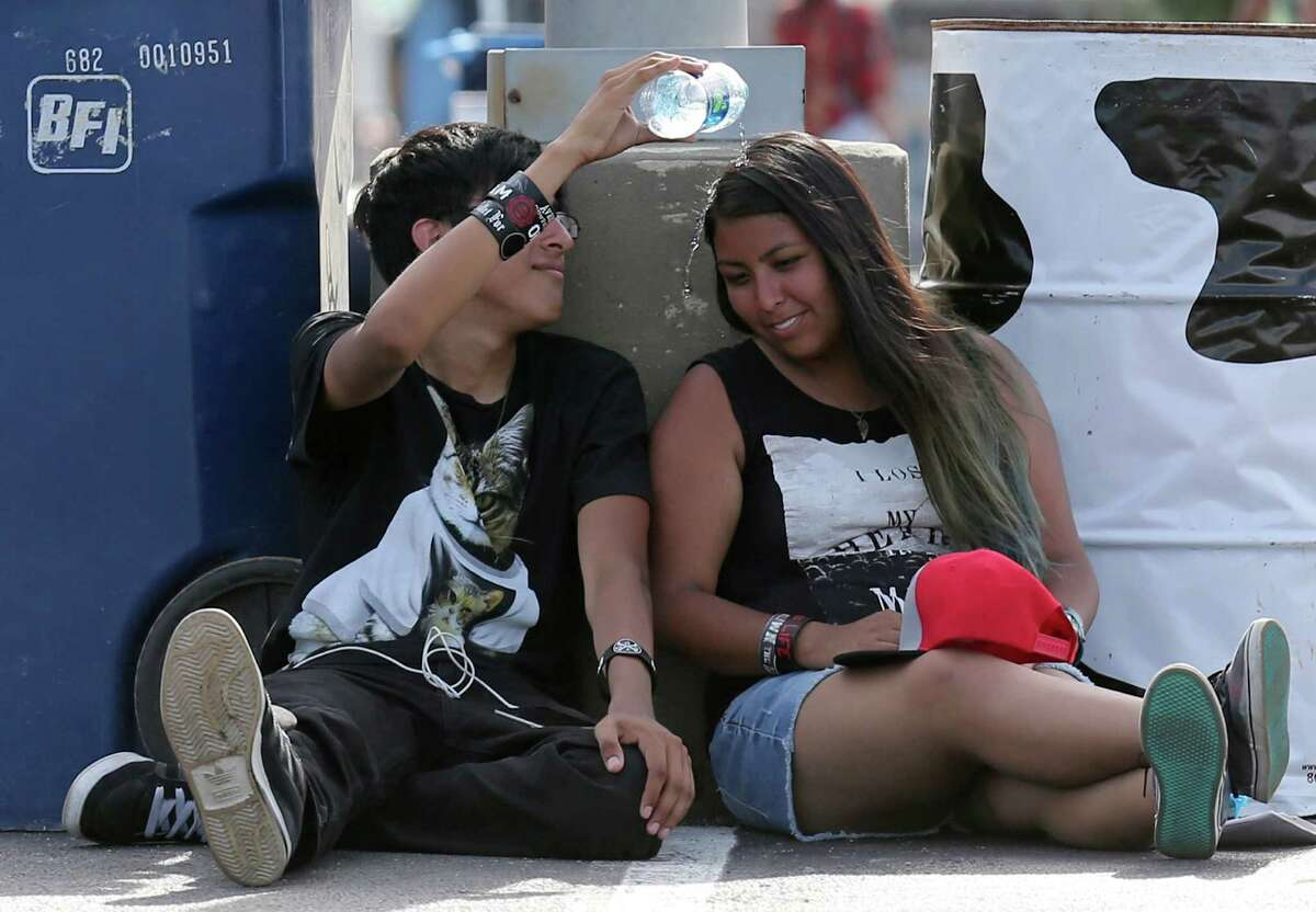 Jose Mendiola (left) and Suzanna Contreras try to stay cool while attending the Vans Warped Tour held Sunday June 28, 2015 at the AT&T Center.