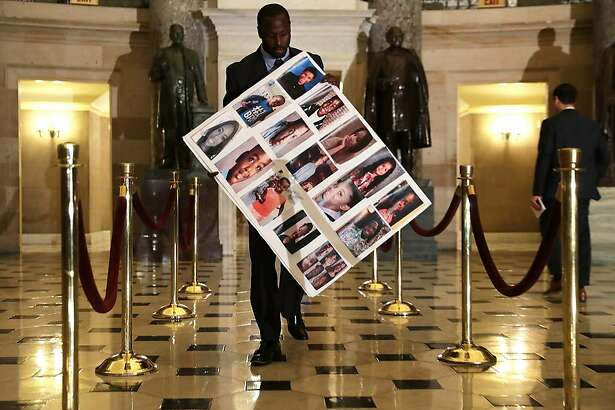 WASHINGTON, DC - JUNE 22:  Charles Bolden, staff assistant of Rep. Robin Kelly (D-IL), holds a poster with pictures of gun violence victims from Chicago as he walks towards the House Chamber June 22, 2016 on Capitol Hill in Washington, DC. House Democrats are staging a sit-in on the House floor to demand Speaker Paul Ryan (R-WI) not to recess the House without voting on legislation including the bipartisan 'No Fly, No Buy' legislation and a universal background check bill.  (Photo by Alex Wong/Getty Images)