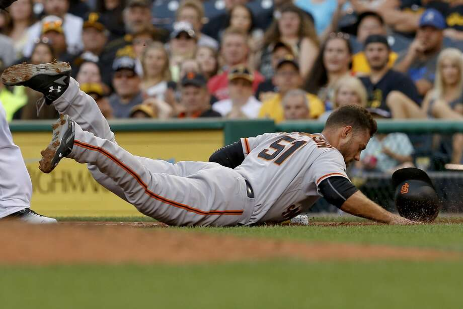 Thursday's No. 3 hitter, Mac Williamson, dives back to firsts base to avoid a double play Wednesday night. He reached base four times. Photo: Keith Srakocic, Associated Press