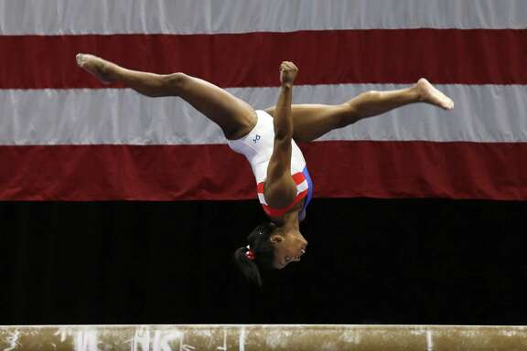 Simone Biles flips across the beam during a practice session on Wednesday. Biles is favored to win a spot on the Olympic team.