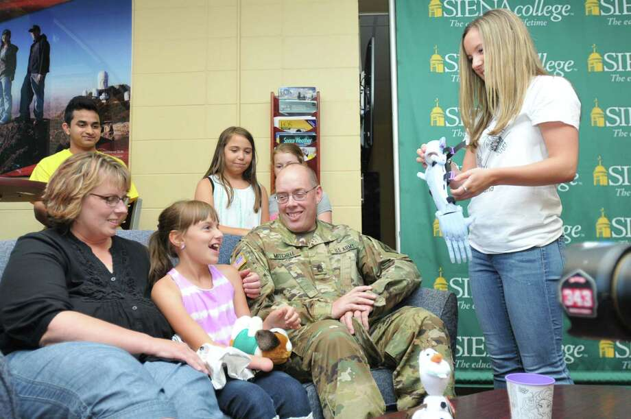 """Siena College senior Alyx Gleason presents 9-year-old Karissa Mitchell of Stillwater with a 3D-printed """"Frozen""""-themed prosthetic arm designed and created by Gleason and the eNABLE Siena chapter of Enabling the Future on June 22, 2016. (Photos provided by Siena College)"""