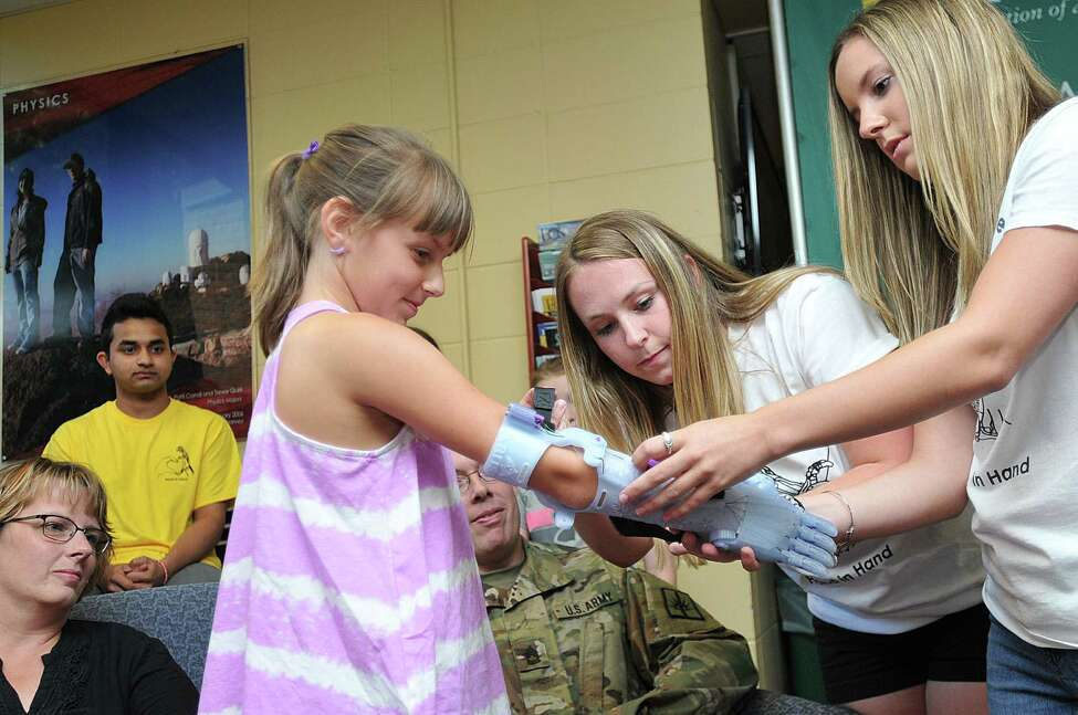 Siena College students Alyx Gleason, right, and Miranda Marnes help 9-year old Karissa Mitchell of Stillwater put on a