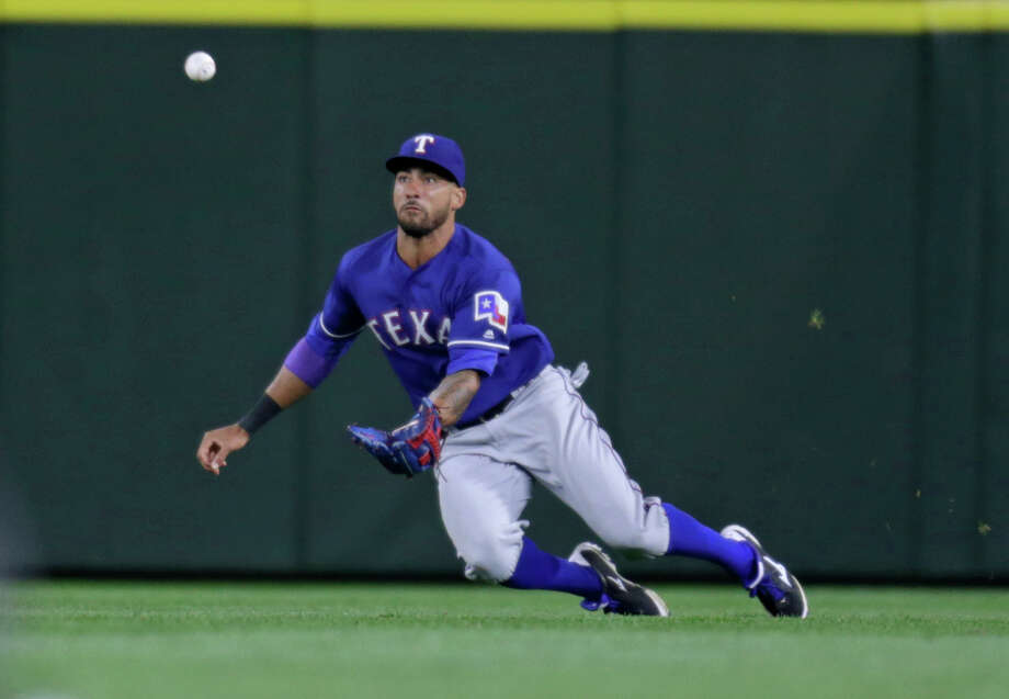 Texas Rangers left fielder Ian Desmond dives for a ball hit by the Mariners' Robinson Cano on June 11, 2016, in Seattle. Photo: John Froschauer /Associated Press / FR74207 AP