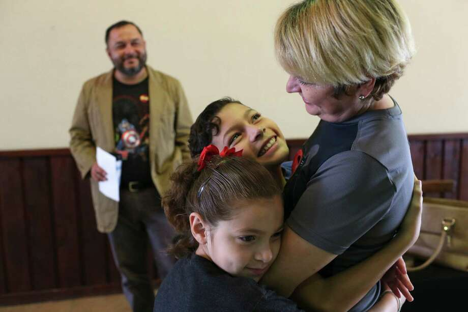Yvanna Garza, 7, and her brother, Abraham, 11, hug their mother, Myrna Garza, 42, after a FatherÕs Day service at Abundant Life Church of God north side campus, June 19, 2016. Garza and her husband, Homero, 42, in back, are undocumented immigrants from Nuevo Rosita, Mexico but their two children are U.S. citizens. They would be protected from deportation by an executive order signed by President Barak Obama creating the Deferred Action for Parents of Americans and Lawful Permanent Residents, (DAPA) in November 2014. The executive order also expanded the Deferred Action for Childhood Arrivals, (DACA) program. The state of Texas sued and was able to block the implementation of the order and the case is now before the U.S. Supreme Court. It is expected to rule on the case by late June. Photo: JERRY LARA, Staff / San Antonio Express-News / © 2016 San Antonio Express-News