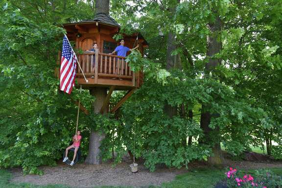 Lexi Goodman, 10, Lucas Goodman, 8, and Devin Goodman, 14, (left to right) play at their tree house in their backyard. Their dad Barrett Goodman built it in October 2010, at a cost of cost more than $20,000.