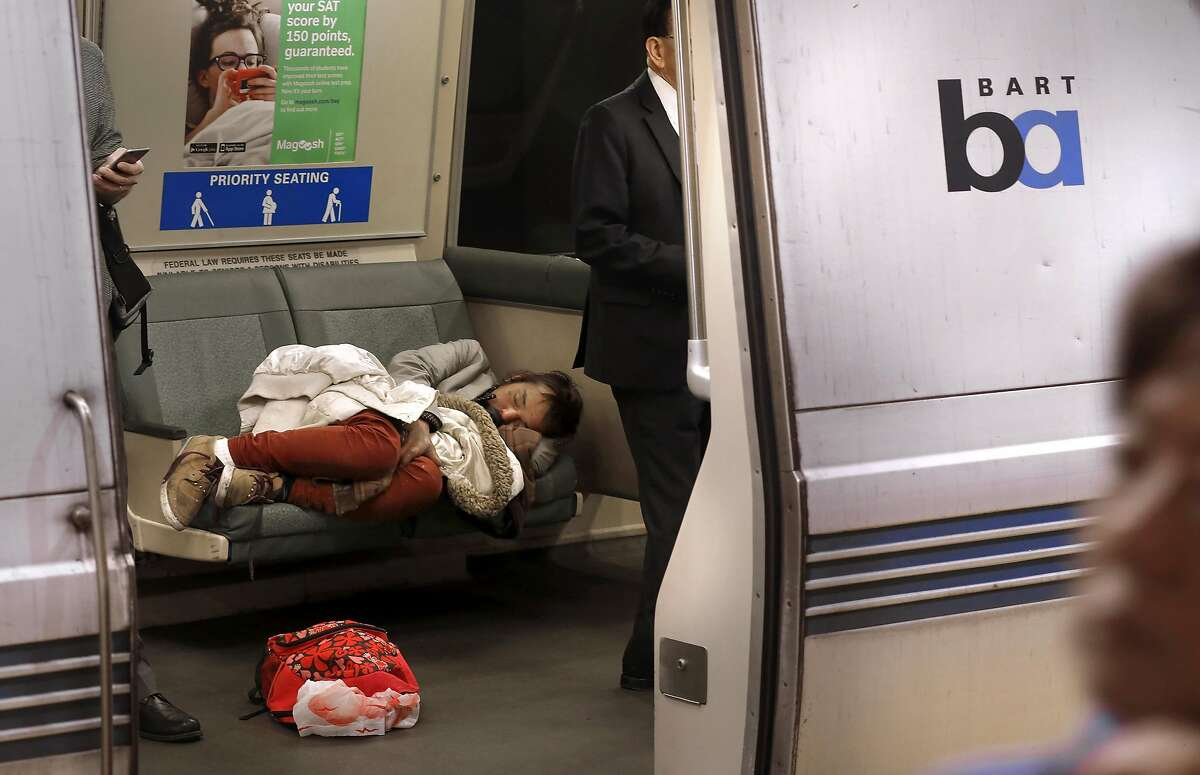 A passenger gets some shut eye taking up more than a single seat along the BART system in San Francisco, California, on Thurs. June 23, 2016. BART is unveiling its system for fining passengers who take up more than a single seat on a train.