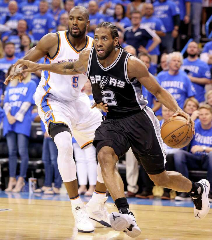 Spurs' Kawhi Leonard drives around the Thunder's Serge Ibaka during second-half action of Game 6 in the Western Conference semifinals on May 12, 2016 at Chesapeake Energy Arena in Oklahoma City.