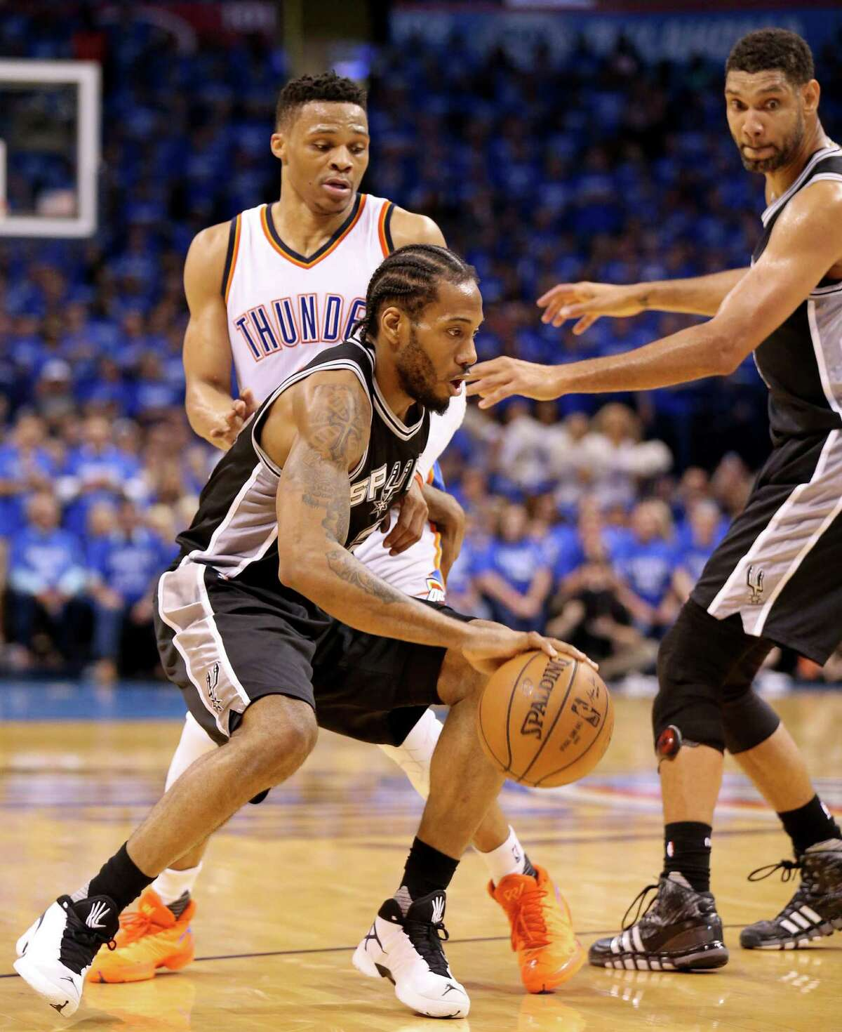Spurs' Kawhi Leonard looks for room around Oklahoma City Thunder's Russell Westbrook as Tim Duncan moves in on the play during second-half action of Game 6 in the Western Conference semifinals on May 12, 2016 at Chesapeake Energy Arena.