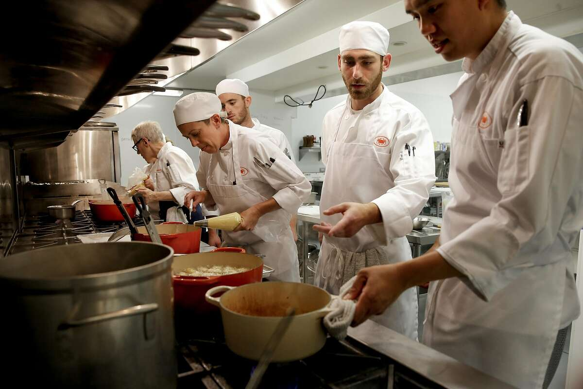 Chef-instructor Catherine Pantsois (far left, facing away) works with students Jamie Gabriel (left), Jason Lauer, Josh Liebeskind and Richard Vi as they prepare potatoes at the San Francisco Cooking School.