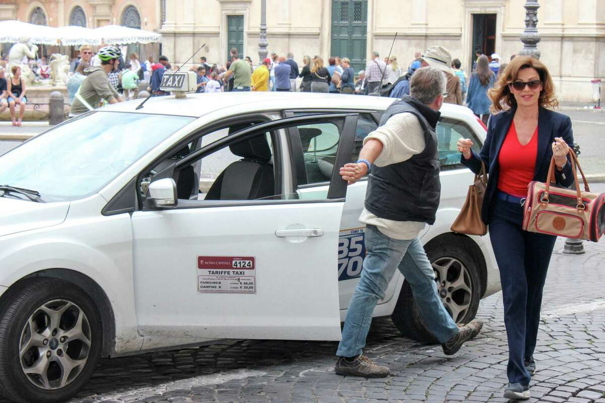 """Rome taxis may be confusing for visitors, but look for white cars with """"taxi"""" on the top and prices on the side door."""