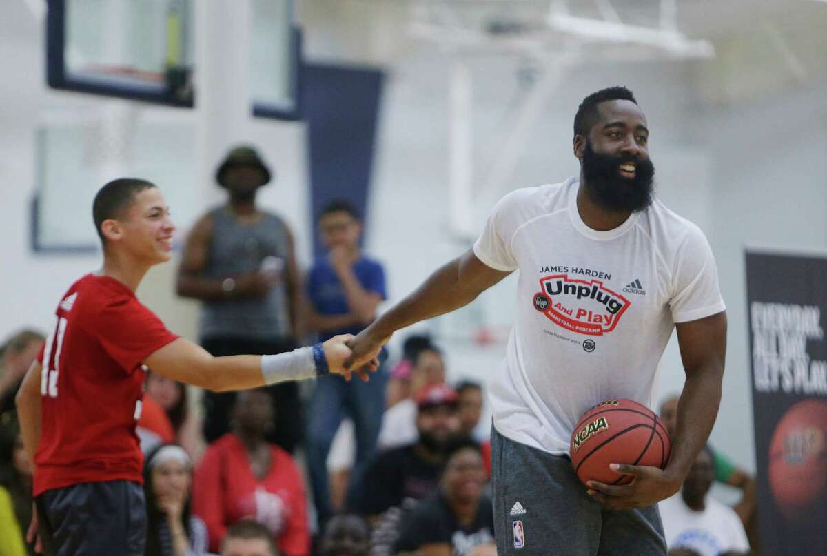 James Harden congratulates a camper during an elimination game at the James Harden Basketball ProCamp,Thursday, June 23, 2016, in Houston.