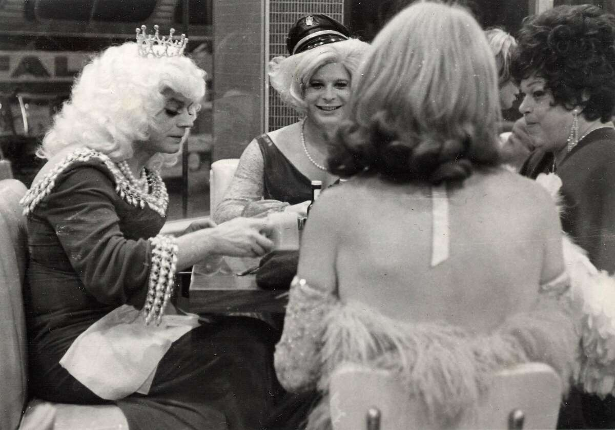A late-night scene in Gene Compton's Cafeteria. The cafeteria was a popular destination for queer people of all kinds: hustlers, queens, hair fairies. This photo shows an Imperial Court of San Francisco event at the cafeteria. The date and names of the subjects are unknown.