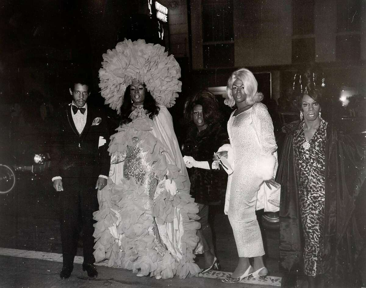 A photo circa 1965 of people arriving at a drag ball. Events like these were held by the Imperial Court of San Francisco. At the time, it was illegal to dress as women and the most vulnerable were frequently harassed by the police.