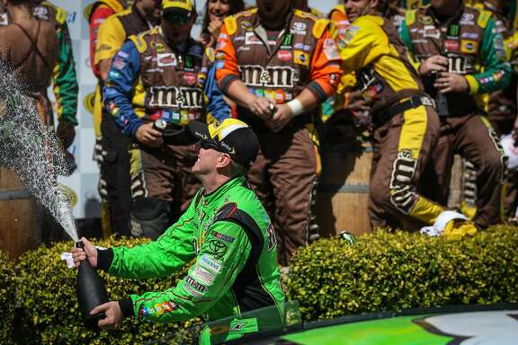 Kyle Busch (in green) celebrates in the Winner's Circle after winning the Toyota/Save Mart 350 race, part of the NASCAR Sprint Cup Series, at Sonoma Raceway in Sonoma, California, on Sunday, June 28, 2015.